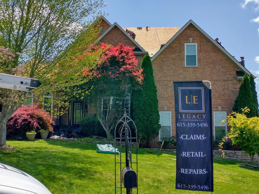Nice home getting new roof with Legacy Exteriors banner in front